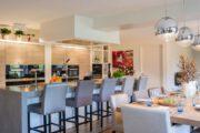 Woonkeuken met grote bar en lange eettafel in groepsaccommodatie