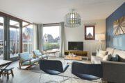 Lichte woonkamer met zithoek met fauteuils, schommelstoel en beige bank in vakantiehuis van Landal