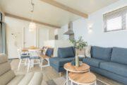 Langwerpige woonkamer met grijze hoekbank en eethoek met bankje en drie stoelen