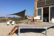 Tiny house op het strand met terras en ligstoelen