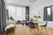 Ronde eettafel met stoelen en zithoek met witte bank en twee fauteuils
