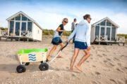 Gezin met bolderkar op het strand bij de strandhuisjes