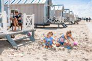 Kinderen spelen in het zand voor de strandhuisjes