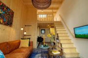 Zithoek en trap naar het slaapgedeelte in het tiny house