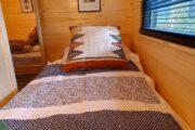 Close up van een eenpersoons bed in het tiny house