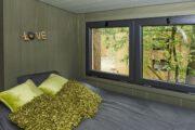 Tweepersoons bed met raam ernaast met zicht op de natuur