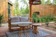 Overdekt terras met lounge bankje en vloerkleed voor het tiny house