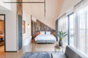 Slaapkamer met vrijstaand bad en grote ramen