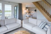 Licht ingerichte woonkamer met doorkijk naar de keuken van het vakantiehuis
