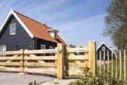 Zwart vakantiehuis met houten hek, in Zeeland