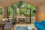 Vakantiehuis met aan een kant een gevelgroot raam met zicht op het bos