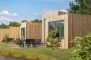 Een rijtje met houten lodges op een vakantiepark