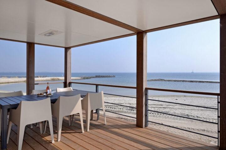Overdekt terras aan het strand met eettafel met 6 stoelen