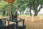 Terras met hangstoel en uitzicht over de weilanden