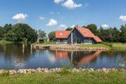 Grijze vakantiehuizen met oranje daken aan de waterkant,