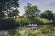 Bootje op rivier de Regge met op de achtergrond 2 boomhutten