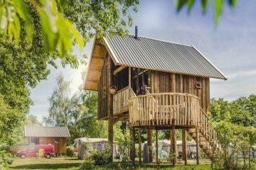 Houten boomhut in een groene omgeving