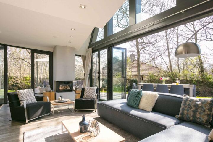 Grote woonkamer met zonlicht en een grote open schuifpui