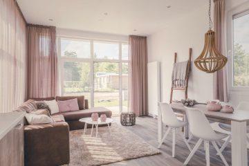 Lichte woonkamer met een eettafel, bank en grote ramen