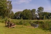 Bomen, gras en een rivier bij het vakantiehuis