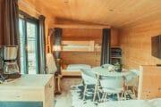 Zithoek in een tiny house met op de achtergond een stapelbed