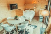 Zithoek in een tiny house met op de achtergond een tweepersoonsbed