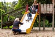 Kind die van de glijbaan gaat in de speeltuin bij de vakantiehuisjes
