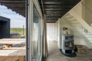 Houtkachel en schuifpui met zicht op de hot tub bij het vakantiehuis