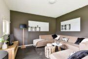 Woonkamer met hoekbank en een bruine muur