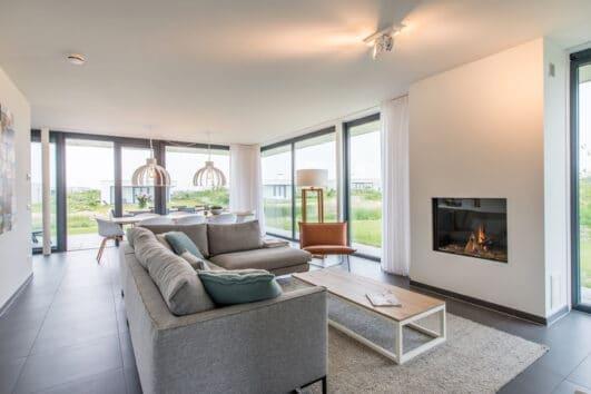 Lichte woonkamer met sfeerhaard en grote ramen in de Z'AND villa