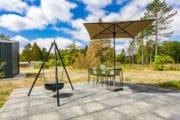 Terras met driepoot met pan en parasol boven de eettafel