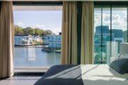 Slaapkamer met open schuifpui en zicht op het water