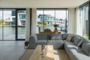 Luxe woonkamer met zicht op de watervilla's door de grote ramen