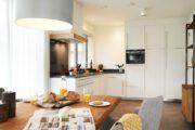 Strakke witte keuken met eettafel met ontbijt