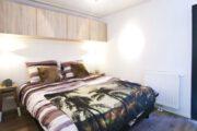 Tweepersoons bed in de slaapkamer van het tiny house
