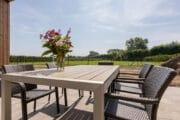 Tuin met eettafel en uitzicht op een grasveld