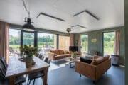 Ruime woonkamer met zithoek met twee zitbanken, grote ramen
