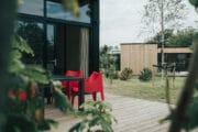 Terras met rode terrasstoelen bij het vakantiehuis
