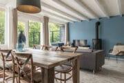 Woonkamer met eettafel, zithoek en houtkachel in het vakantiehuis van Dutchen op Ameland