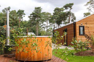Houten huisje met hot tub in de tuin voor een weekendje weg
