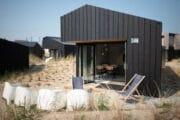 Strak vakantiehuis met zwart hout en witte tuinstoelen